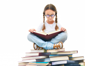 young girl with pigtails and glasses reading atop a pile of books