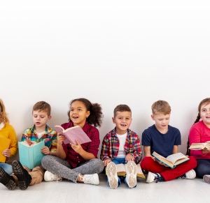 Children reading corss-legged on the floor in a line