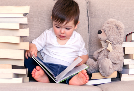 Reading with autistic children - child rading book on sofa surrounded by more books and next to teddy bear