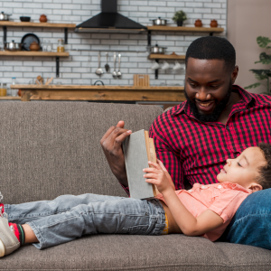 man in a checked shirt on a sofa with his son lying on his lap reading a book together - half term reading tips