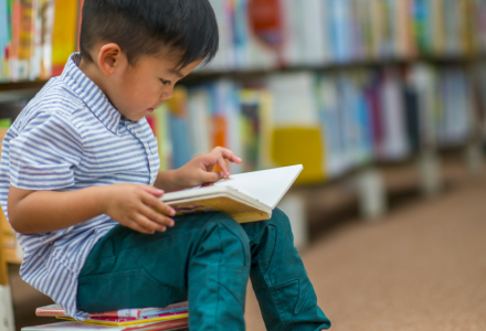 a young independent reader reading a book in a library