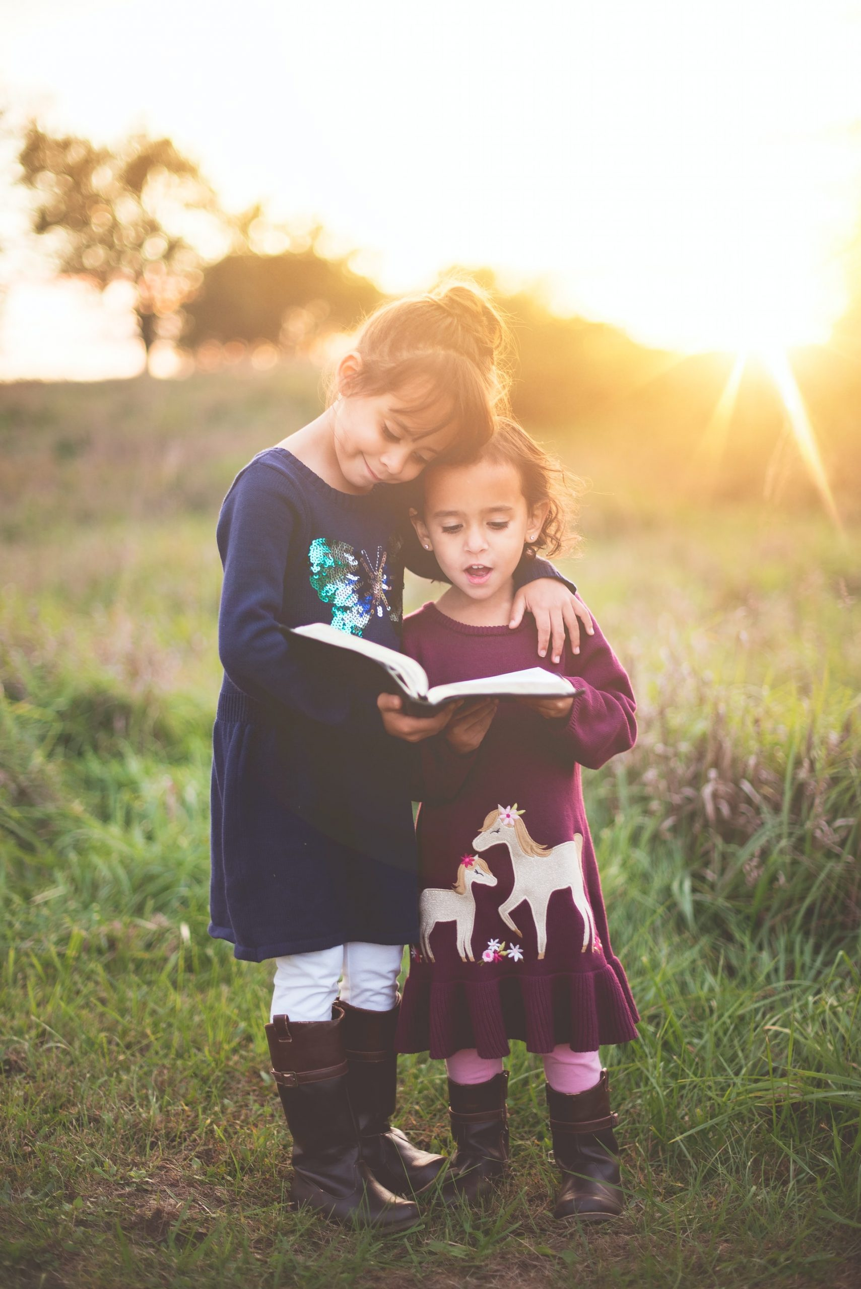 2 young girls reading a book together
